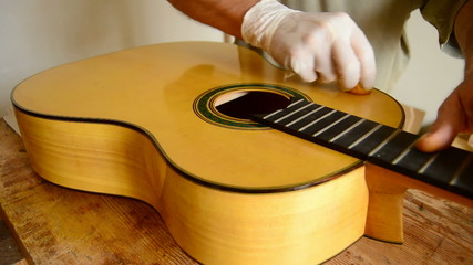 Luthier varnishing a flamenco guitar