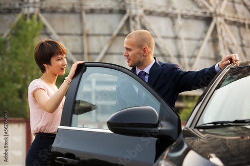 Young business couple talking at the car