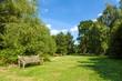 Leinwandbild Motiv Park Bench in Beautiful Lush Green Garden