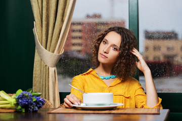 Young woman eating a soup at restaurant