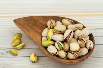 Pistachio nuts with and without shell in wooden bowl