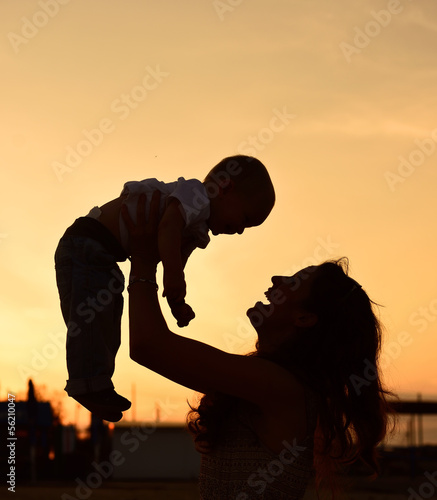 Mother and baby son silhouettes on beach at sunset