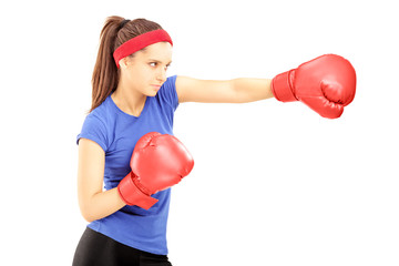 Female athlete hitting with red boxing gloves