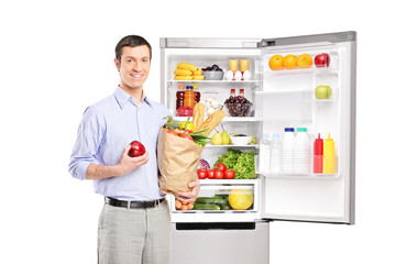 Smiling man with a bag in front of refrigerator full of products