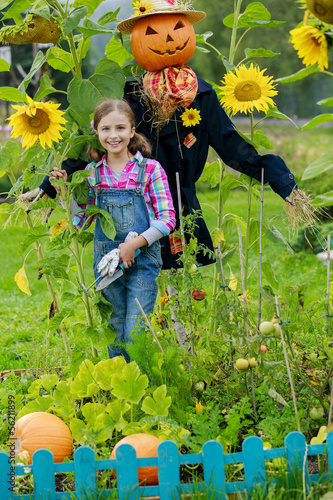Scarecrow and happy girl  in the garden
