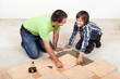 Father and son laying ceramic floor tiles