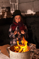 Young homeless boy on the street warming his hands