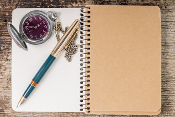Top view of notebook with ink pen and pocket watch
