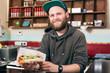 salesman with hotdog in fast food snack bar
