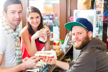 Customers eating Hotdog in fast food snack bar