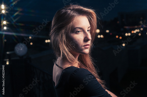 Beautiful lonely woman in the old house against city night