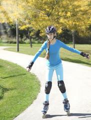 Teenage girl rollerskating in park