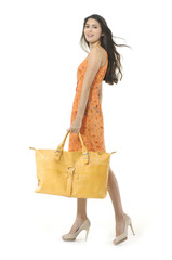 Full body fashion model with big yellow bag walking