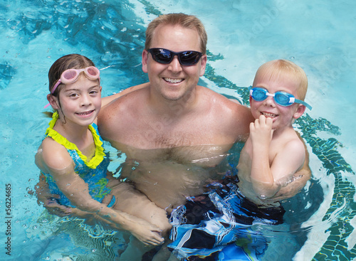 Family playing in the swimming pool together