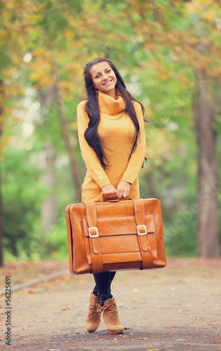 Brunette girl holding suitcase at autumn alley in the park