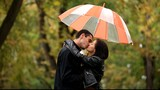 couplewith umbrella kissing outdoor in the park