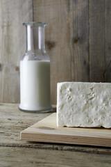 Fresh feta cheese with bottle of milk