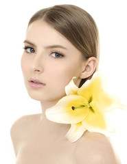 young girl with clean skin on pretty face with lily flower