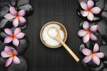 Set of frangipani flower with stones and salt in spoon on mat
