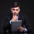 pensive young business man with tablet