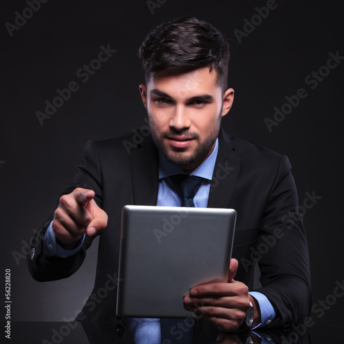 young business man with tablet points at camera