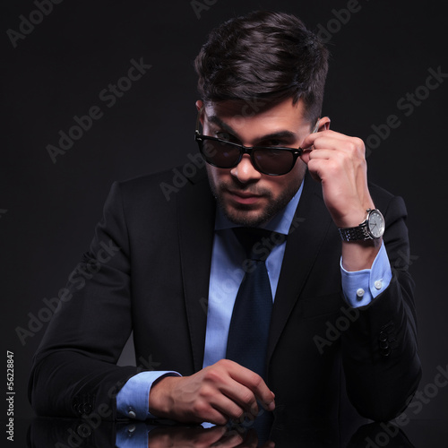 young business man looks over his sunglasses