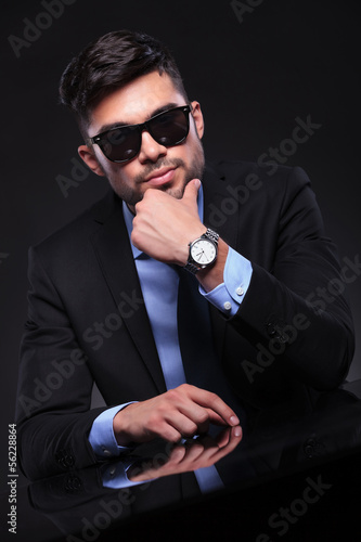 young business man stands with hand on chin at desk