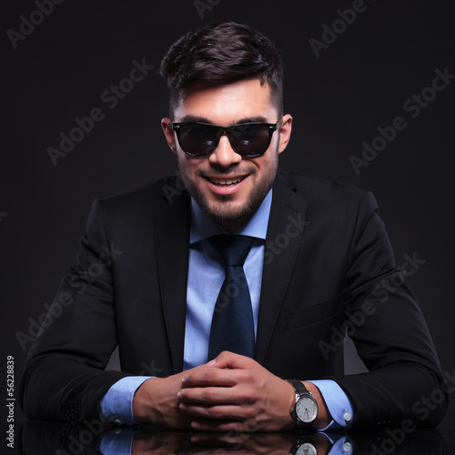 young business man smiles at you