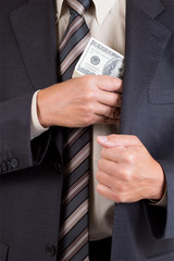 man putting dollars pack into pocket