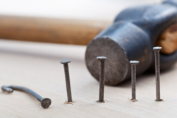 hammer and nails into wooden board