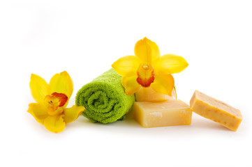 Rolled green towel, soap bar and yellow orchid flower.