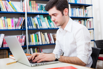 Guy using his laptop in a library
