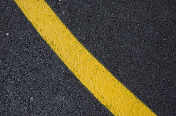 yellow curved line painted on asphalt background