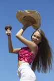 happy longhaired girl dancing with maracas and hat