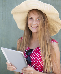 happy girl in hat holding the tablet computer