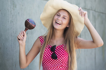 Beautiful smiling girl holding maracas and hat