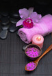 pink orchid on towel and stones ,candle, salt in bowl on mat