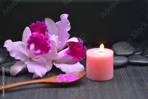Beautiful pink orchid and stones ,candle, salt in bowl on mat