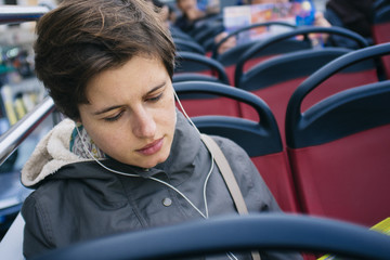 young woman commuter listening to music on the bus