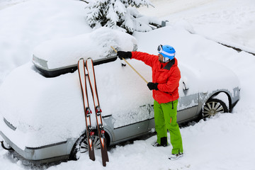 Skier man is shoveling the car of snow