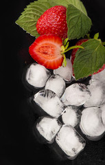 ice cubes, mint leaf, fresh strawberry on black
