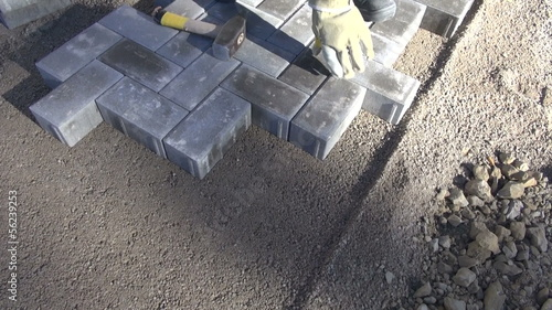 mason worker making new sidewalk pavement with stone bricks