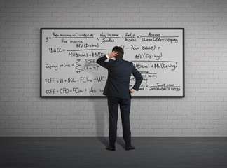 Businessman standing in front of board with formulas