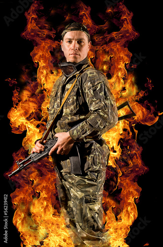 Soldier stands with a gun in his hand  in a burning fire