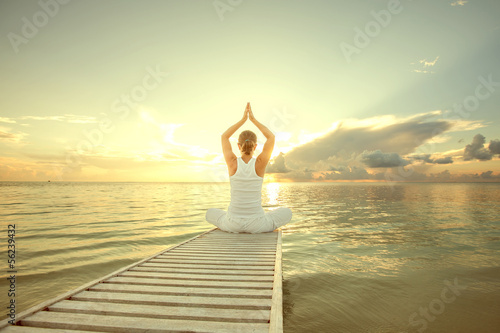 Caucasian woman practicing yoga at seashore - 56239432