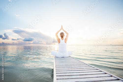 Stampa su Tela Caucasian woman practicing yoga at seashore