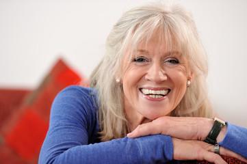 Lächelnde Seniorin entspannt auf dem Sofa