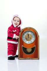 Small boy in Santa suit plays with vintage clock in white studio