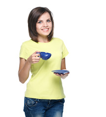 Attractive young woman in a yellow shirt. Holds a blue cup.