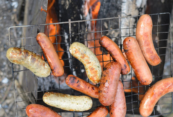 Sausages cooking on a portable barbecue